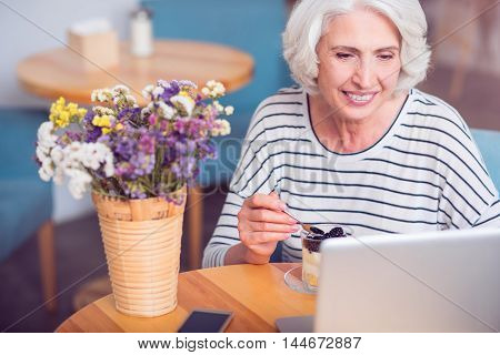 Have a tasty meal. Cheerful delighted senior woman eating dessert and using laptop while resting in the cafe