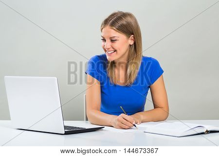 Beautiful female student using laptop and studying.