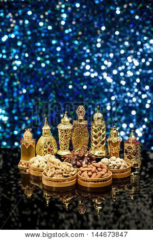 Ramadan and Eid theme background with lanterns, nuts and perfume bottles against a blue glitter background