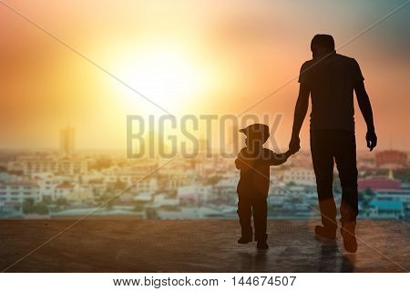 Child baby holding an adult's hand. Father and son on a walk. Happy lovely baby on a wooden terrace with sun sets blurred. Little baby having fun time activity .silhouette concept.