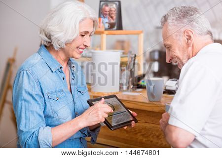 Contemporary users. Positive content senior couple smiling and usin tablet while standing in the cafe