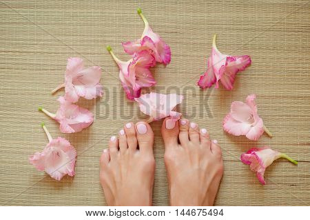 Spa composition - foot female with a light pink nails and pink flowers on a straw mat