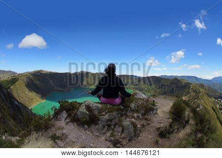 Young woman doing yoga on the edge of the crater of the Quilotoa  volcano