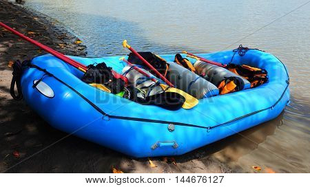 blue inflatable rafting boat full of equipment on the river bank