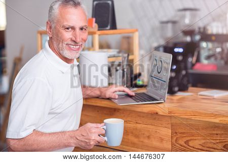 Favorite beverage. Positive smiling senior man drinking coffee and using laptop while resting in the cafe