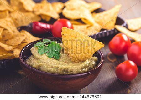 Fresh guacamole sauce with corn chips closeup