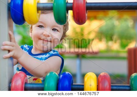 Little boy playing on the playground. Summer Good weather colorful toys