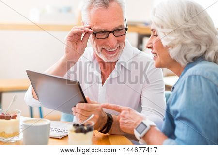 Happy together. Cheerful delighted senior couple smiling and using tablet while resting in the cafe