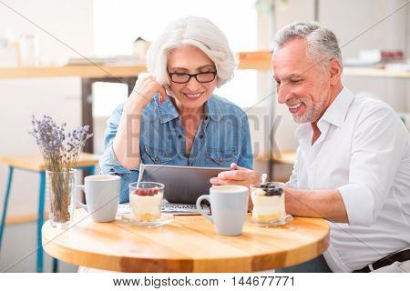 Warm atmosphere. Positive content smiling senior couple sitting at the table and using tablet while having breakfast