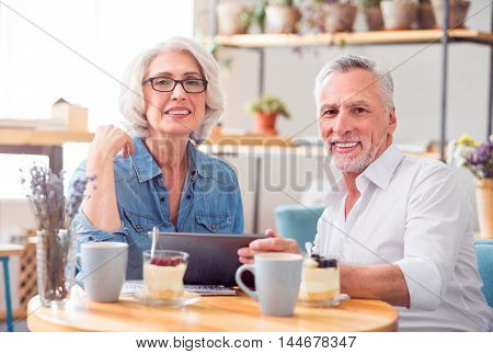 Rise your mood. Cheerful glad senior couple resting sitting at the table and holding tablet while having breakfast
