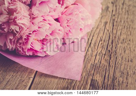 Bouquet of pink peonies wrapped in pink paper on a wooden background (vintage)