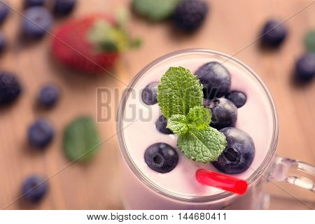 Glass of blueberry smoothie with mint on wooden table closeup top view