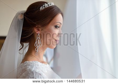 Beautiful bride in white wedding dress standing in her bedroom and looking in window, she waits for the groom