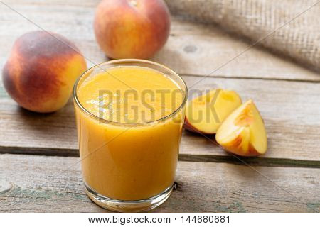 Glass of peach fresh on wooden table