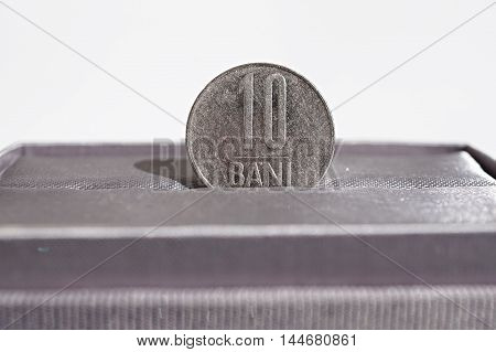 Macro detail of a metal coin of ten Bani (Romanian currency RON also called Lei or Leu, subdivided into bani) placed in the gift box as a symbol of luxury and highly appreciated currency of Romania
