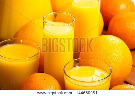 Oranges and glasses of  juice on table