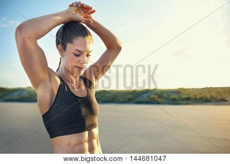 Fit young woman with toned abdominal muscles doing warming up exercises before a workout raising her arms above her head rural road with copy space