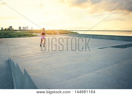 Healthy young woman enjoying a morning run jogging across an open promenade towards a flight of steep concrete steps in the glowing light of the rising sun