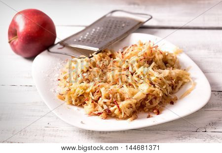 Grated apple on plate on wooden table
