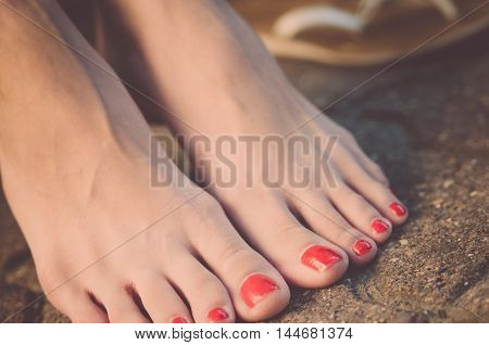 Women's legs barefoot on the pavement close up. Nails are made up with red lacquer (vintage)