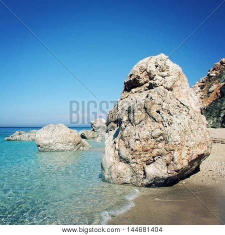 Huge boulder on the small beach near Adrasan. Calm blue sea and rocks. Clear sky. Vintage effect image. Rocky shore. Antalya Province Turkey. Square format photo.