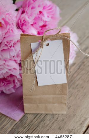 Package of kraft paper with a tag to write on a wooden table next to a bouquet of flowers