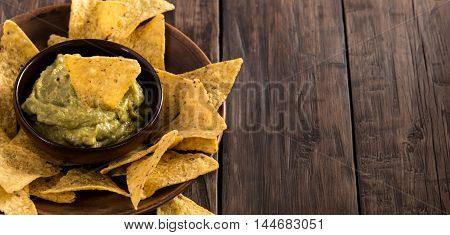 Homemade fresh guacamole sauce with corn chips from left side of rustic wooden table