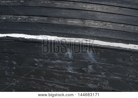Some old black and weathered ship planks with damages