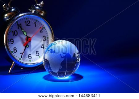 Glass globe near alarm clock on nice dark background