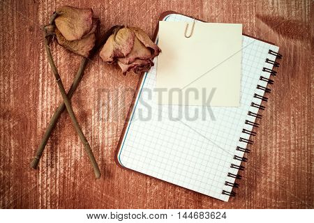 Old roses and notebook with blank sticky note
