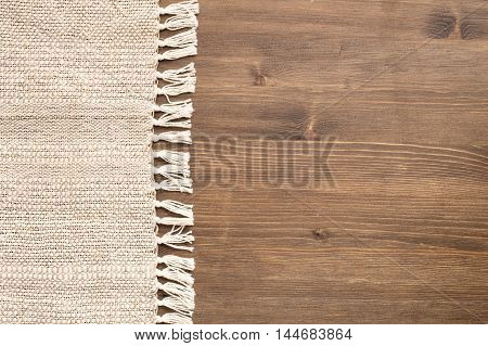 Handmade tablecloth at left side of wooden background top view