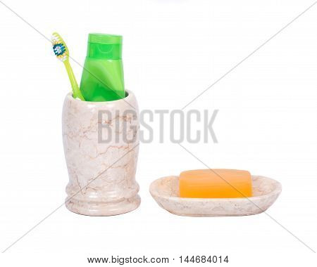 Goat milk soap, toothbrush, toothpaste, beige marble dish and cup on white background