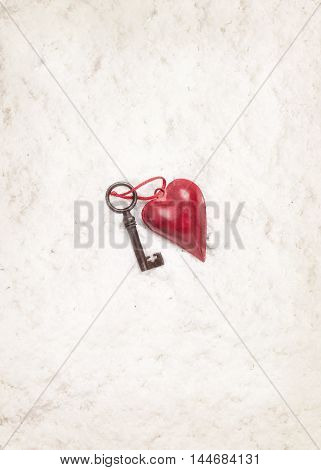 Vintage heart decoration and old key at center of white snow background. Concept of Valentine's day.