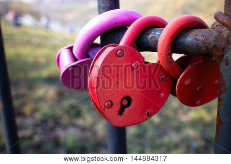 Red heart-shaped locks on fence. Relationship concept