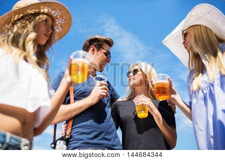 A photo of young happy couple partying outside with their friends and drinking beer. They're looking at each other with love.