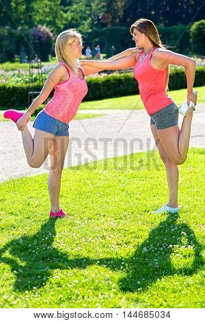 Two gorgeous ladies in gray shorts and bright red tops holding each other up for balanced yoga poses outside at sunny park