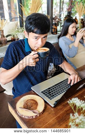 Portrait Of Handsome Asian Smiling Man Enjoying Coffee In Cafe While Sitting At The Wooden Table Wit