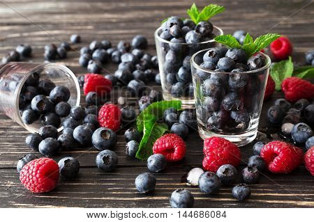 Blueberries, Raspberries And Mint At Black Wooden Table.