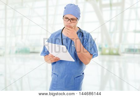 worried doctor looking to his notes, at the hospital