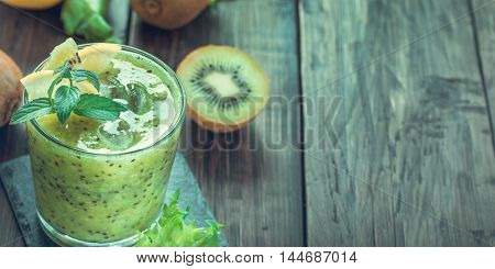 Energy morning  green smoothie with kiwi and lemon from left side of old wooden table with copy space.Toned.