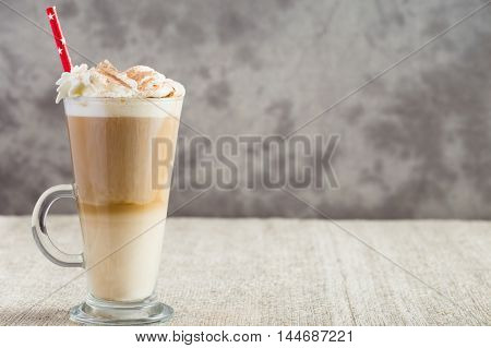 Latte coffee from left side of wooden table with copyspace