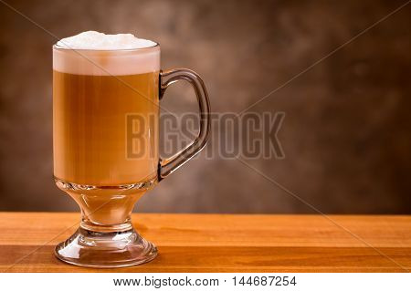 Latte coffee on wooden table with copyspace