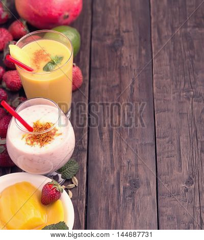 Mango and strawberry smoothies at left side of old wooden table with copy space