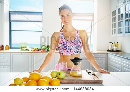 Fit healthy young woman with a lovely smile standing in her kitchen preparing fruit juice form a selection of fresh fruit on the counter