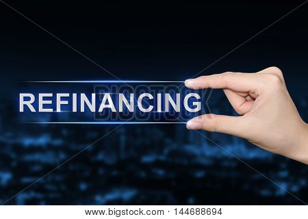 hand pushing refinancing button on blurred blue background