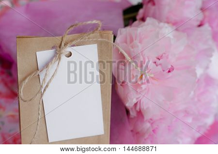 Kraft bag with an empty tag close to blooming pink peonies