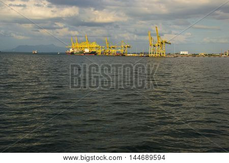 Photo of the Cargo ship terminal. Container Terminal. Industrial port on horizont. Shipping.