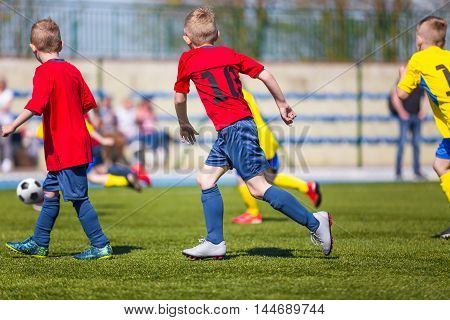 Young soccer football players. Boys playing soccer match on sports field