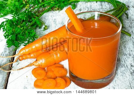 fresh-squeezed carrot juice with vegetables and sliced segments on rustic wooden background