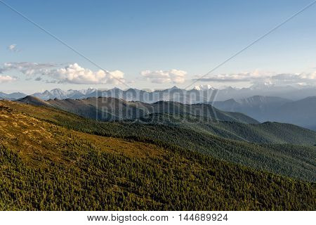 Scenic top view on the mountain peaks and slopes of the mountains covered with forests on the background of blue sky and clouds at sunset